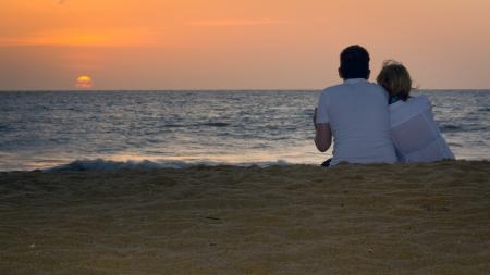 사랑하는 부부는 모래 사장에서 일몰을 즐기고 스톡 콘텐츠