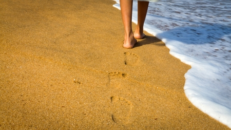 footprint: Young woman walking on a sandy beach