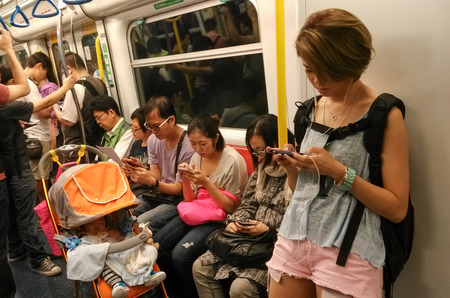 Unidentified passengers use their mobile phones in a subway train  Mobile phones and tablets are used for people to entertain and view information when they take public transportation   Editorial