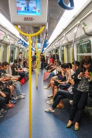 Unidentified passagiers rijden Mass Transit Railway dat is de snelle doorvoer spoorwegsysteem in Hong Kong en een van de meest winstgevende van dergelijke systemen in de wereld