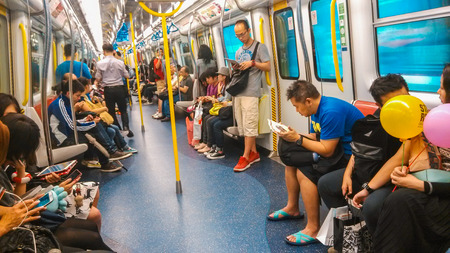telephones: Unidentified passengers ride Mass Transit Railway which is the rapid transit railway system in Hong Kong and one of the most profitable such systems in the world