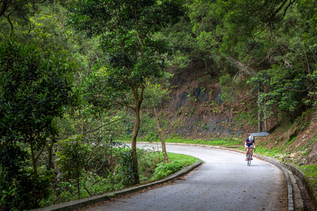 An Unidentified Man Cycling in Famous MacLehose Trail Section 9 in Hong Kong, China  photo