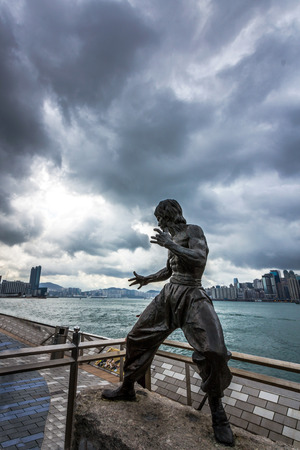 Bruce Lee statue in Avenue of Stars in Tsim Sha Tsui before a cyclone  Typhoons regularly skirt the city in Summer, causing heavy damages including injuries and deaths