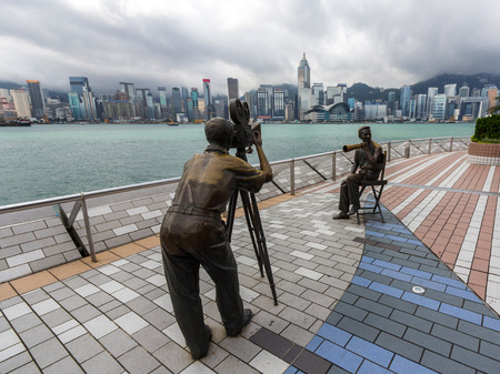 famous industries: Statue and skyline in Avenue of Stars in Hong Kong, China  The promenade honors celebrities of the Hong Kong film industry as the famous city attraction