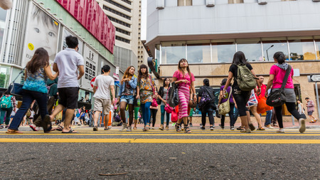 People crossing a busy street in Causeway Bay  Hong Kong is one of the most densely populated areas in the world