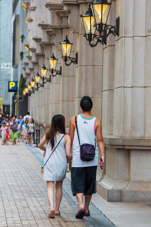 sha: An unidentified Chinese couple walk in a street of Tsim Sha Tsui, Hong Kong