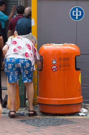 overpopulation: Old women collecting bottles from garbage bins in Hong Kong. 1.3 million Hongkongers still live in poverty.