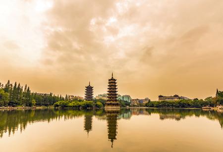 太陽と桂林で夕暮れ時に月ツイン塔