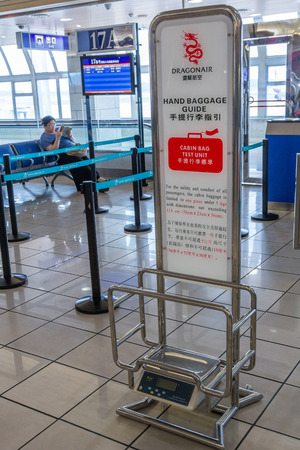 belongs: An equipment belongs to Dragonair which checks the size and weight of hand luggage before boadring to the fights in Guilin Liangjiang International Airport.