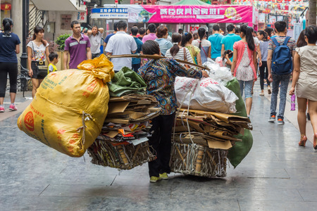 A poor and old Chinese woman carrying lots of recycling materials. More than 82 million rural Chinese got by on less than 1 a day by 2014.