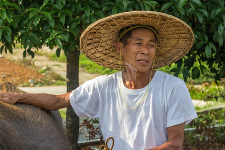 employing: An unidentified old farmer in Yangshuo China. Agriculture is a vital industry in China employing over 300 million farmers.