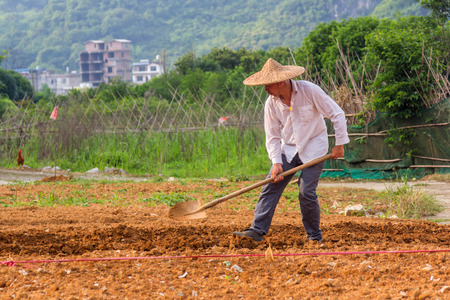 employing: A Chinese farmer is working on fields next to Yulong river in Yangshuo. Agriculture is a vital industry in China employing over 300 million farmers. Editorial