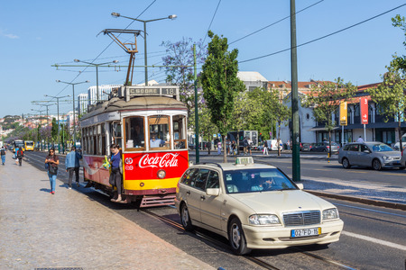 presently: A vintage tram and a modern taxi cab in Lisbon, the capital of Portugal. The Lisbon tramway network operates since 1873 and presently comprises five urban lines.