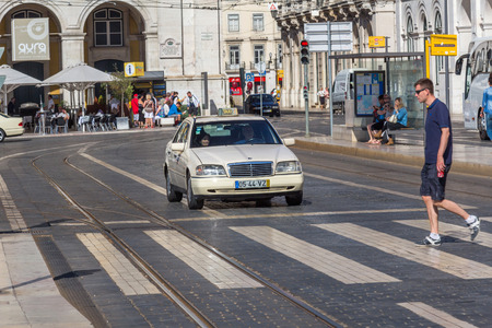 reported: An unidentified pedestrian cross a road in Lisbon, Portugal. In year 2012, 9.7 road fatalities per 100,000 inhabitants were reported in Portugal.