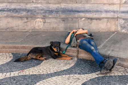 homeless person: A homeless person sleeping on the ground with his dog sitting beside him. By Jan 2015 19.5 of Portuguese population were at risk of poverty after social transfers.