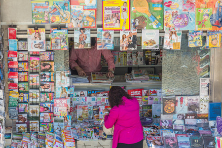 playboy: An unidentified woman buys newspapers from a small shop next to Cais do Sodre train station in Lisbon Portugal.