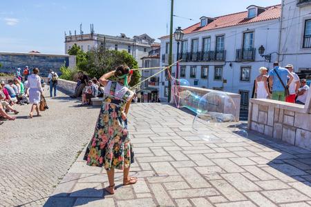 european culture: A person entertain the crowd gathered at Lmiradouro Santa Luzia in Lisbon Portugal. Outdoor entertainment is the part of European culture. Editorial