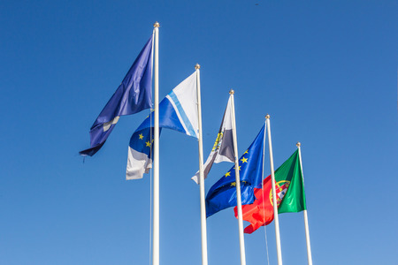 waiving: Flags of European union Portugal and Lisbon waiving in the sky.