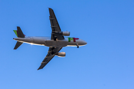 headquartered: TAP Portugal flight flying over Lisbon sky. It is the flag carrier airline of Portugal headquartered at Lisbon Portela Airport which also serves as its hub.