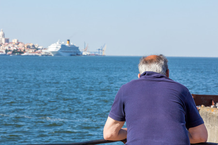 old person: An old person looking at a passenger ship docked at Tagus river, Lisbon, Portugal