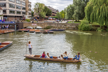 slipway: Punting in summer on the river Cam in Cambridge, England. DoubleTree hotel by Hilton can be seen in the background.