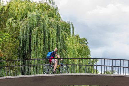 punting: An unidentified cyclist resting on Garret Hostel Lane bridge over river Cam. Punting is one of the main outdoor activities in summer in Cambridge, England. Editorial