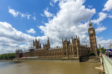 white clouds: UK Parliament next to Thames river in London, England