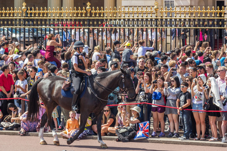 police officer: A female police officer on a horse controlling crowds in front of Buckingham palace in London, England.