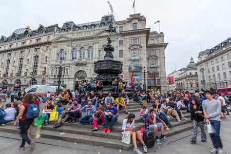 shaftesbury: Tourists sitting on the steps of the Shaftesbury Memorial Fountain in Piccadilly Circus in City of Westminster. Its a road junction and public space of Londons West End.