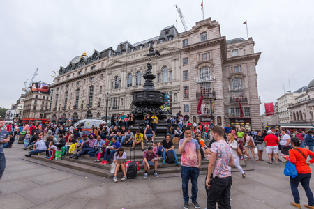 west end: Tourists sitting on the steps of the Shaftesbury Memorial Fountain in Piccadilly Circus in City of Westminster. Its a road junction and public space of Londons West End.