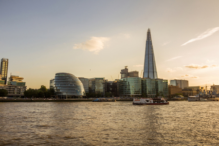 subset: View of the Shard, city hall, and the Scoop over the river Thames at subset in London, England