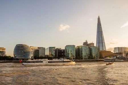 View of the Shard, city hall, and the Scoop over the river Thames at subset in London, England