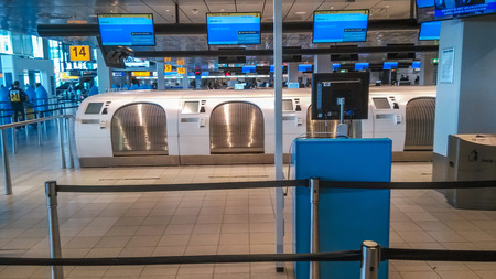 dropoff: AMSTERDAM, NETHERLANDS - MAY 30, 2015: Self-service baggage drop-off machine at Amsterdam Airport Schiphol. It is the main international airport of the Netherlands, located 4.9 nautical miles southwest of Amsterdam.