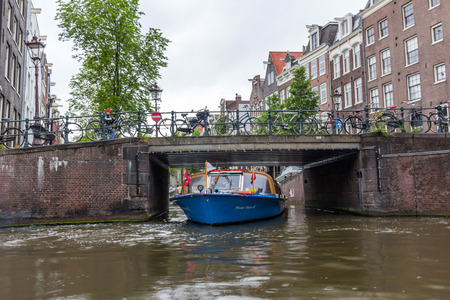 sightseeing tour: AMSTERDAM, NETHERLANDS - MARCH 14, 2016: A sightseeing tour boat in a canal in amsterdam, Netherlands. Amsterdam Canal Cruises are one of the best ways to enjoy the city in a short time.