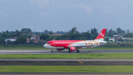 airborne vehicle: AirAsia plane on a runway of Soekarno�Hatta International Airport in Jakarta, Indonesia. AirAsia is the largest airline in Malaysia in fleet size and destinations, the largest low-cost airline in the Southeast Asia.Soekarno-Hatta International Airp