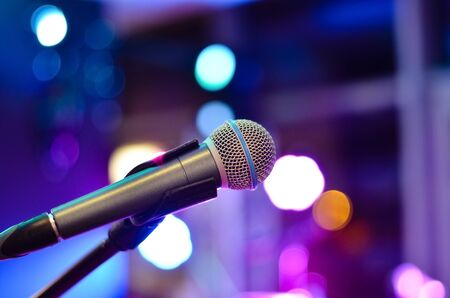 Close-up  of microphone on a defocused  background with multi colored lights at a concert .