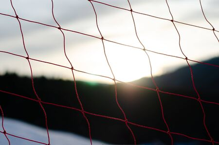 Close up full frame shot of protection net ski fence against sky with lens flare