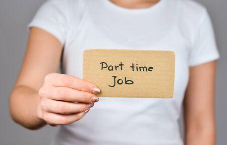 Nahaufnahme der Hand der jungen Frauen, die quadratisches Papppapier mit Teilzeitjob-Phrase handgeschrieben hält.