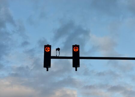 Low angle view of red  traffic lights   with the arrow pointing to ahead  and the left against cloudy blue  sky at sunset . Banque d'images - 132941575