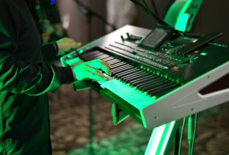 Close-up   hand of a man singing at an electronic synthesizer  at a party during night  with green light  in the background  .