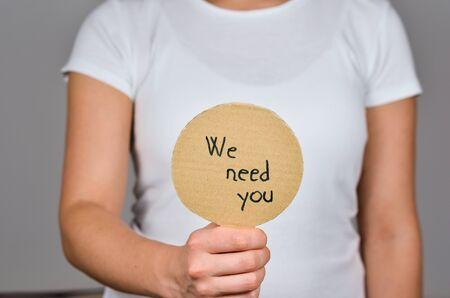 Women hand   holding    round cardboard paper     with handwritten    text  - We Need You.. Reklamní fotografie