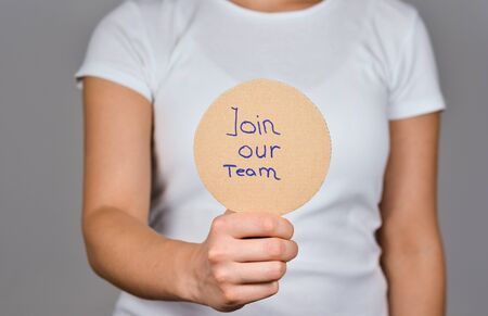 Join our Team sentence handwritten on a round cardboard paper in a women hand.