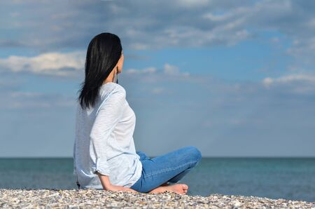Caucasian black hair middle age woman looking at sea against sky A single woman relaxing on beach thinking about future.Summer holiday and vacation Imagens