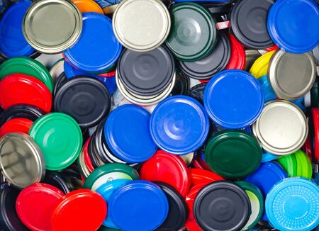 Pile of colored metal caps for glass jars in   a  trash bin for recycling . Selective recycling concept.