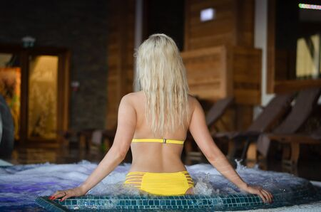Young caucasian blonde girl relaxing  in hot tub  during  winter vacation  holiday Stock fotó - 133308290