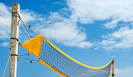 Low angle view   of yellow    filet beach volleyball  against blue sky .  Relaxing activities on vacation at the sea . Banco de Imagens