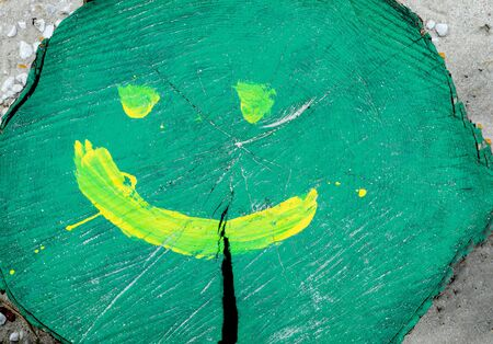 Close-up of green colorful tree trunk hand painted with a  yellow smiling face .  版權商用圖片