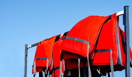 Pile of red lifejackets used by rescuers sitting on a rake   near beach during summer season  against blue  sky .