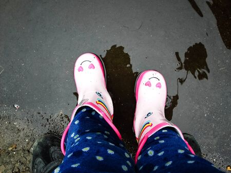 Young  girls with pink boots with his  father  having fun outside in street after rain