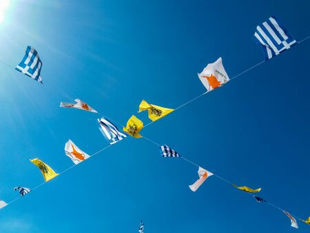 Different national flags hung on wire on a blue sky background .